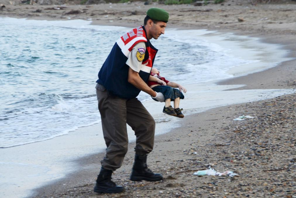 A Turkish gendarmerie carries the body of Aylan Kurdi, 3, who drowned along with his brother Galip, 5, and their mother in a failed attempt to sail to the Greek island of Kos, in the coastal town of Bodrum, Turkey, on Sept. 2, 2015